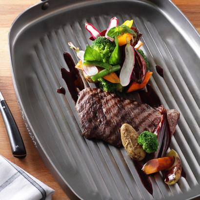 Steak grillé, échalote confite, pommes de terre et jeunes légumes, jus à la bordelaise